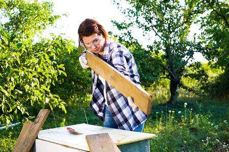 Female carpenter checking evenness of wooden plank