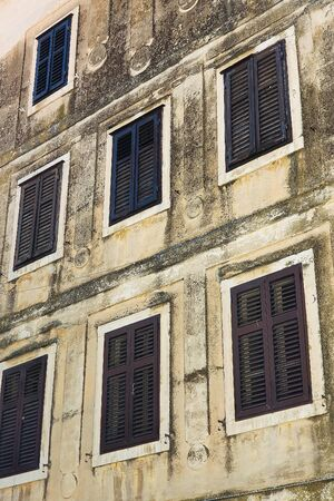 Windows with wooden blinds on old house Stok Fotoğraf - 137891626