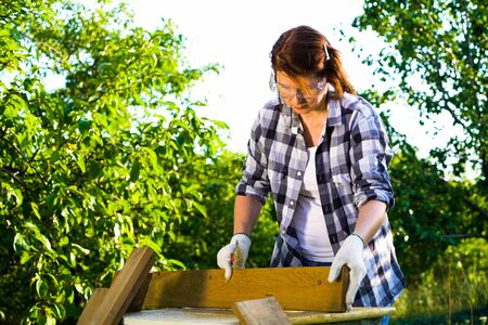Woman carpenter working with wooden planks in backyard 스톡 콘텐츠