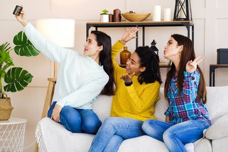 Happy multiracial girls taking selfie photo at home