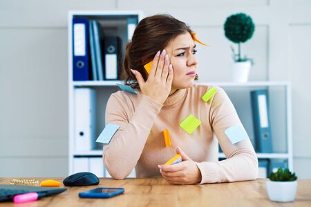 Stressed office girl with stickers on clothes and face sitting at table