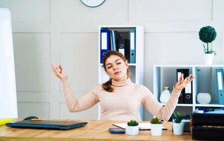 Young girl meditating in zen pose at workplace