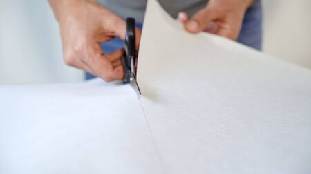 closeup male hands preparing new bended wallpaper roll with scissors on table indoor