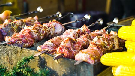 Grilling pork meat and sweet corn at street food stand outside