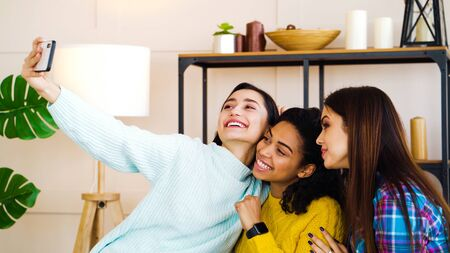 Smiling multiracial female friends taking selfie photo at home