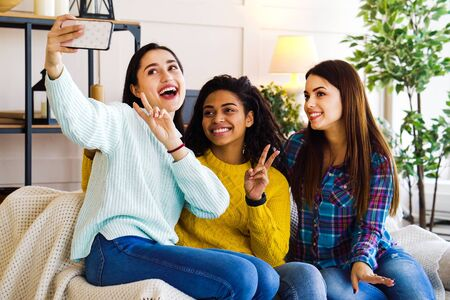 Amiable multiracial girls live streaming from home using smartphone