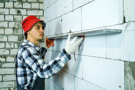 builder pressing construction ruler to interior wall checking its quality Zdjęcie Seryjne