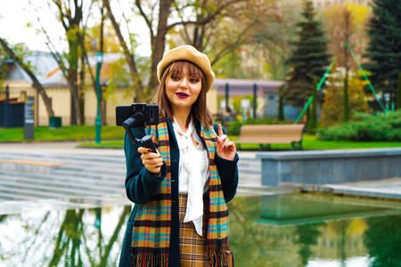 Lovely girl vlogger using steadicam and smartphone for live streaming in park
