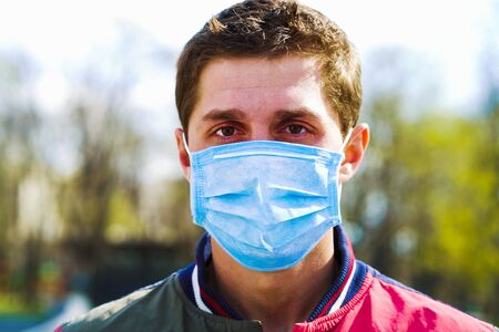Portrait of young man wearing medical mask posing in sunny park