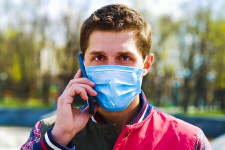 Portrait of man wearing medical mask talking on phone in park