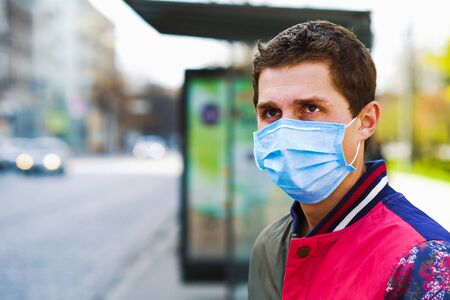 Young man in medical mask waiting for bus on empty bus stop Zdjęcie Seryjne