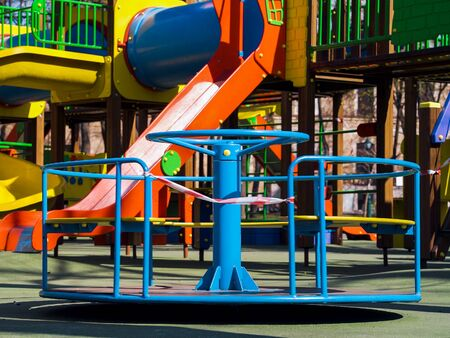 Little carousel with restriction tape on empty playground during coronavirus