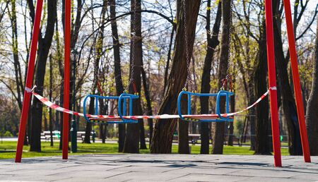 Restriction tape on swings on empty children playground due to covid19 outbreak 스톡 콘텐츠