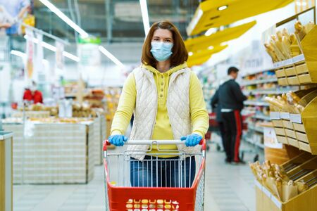 Girl in mask standing at grocery store with shopping cart during covid pandemic