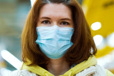 Woman in medical mask posing in shopping center during covid19 pandemic Zdjęcie Seryjne