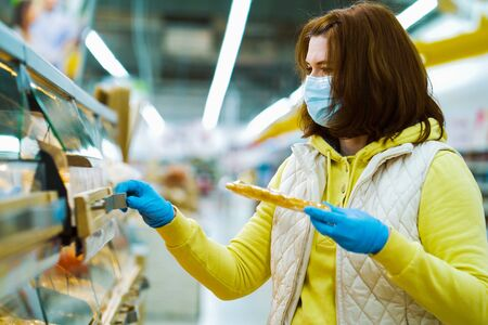 Housewife in medical mask and gloves buying fresh pastry in supermarket