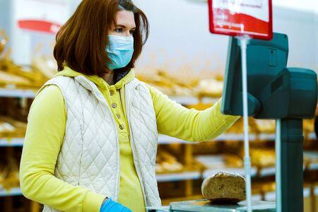 Female customer in medical mask weighing rye bread in supermarket