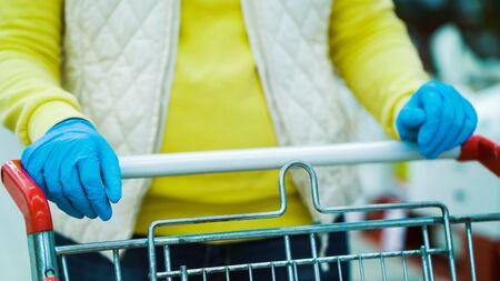 Crop female customer in medical gloves pushing shopping cart in supermarket Zdjęcie Seryjne