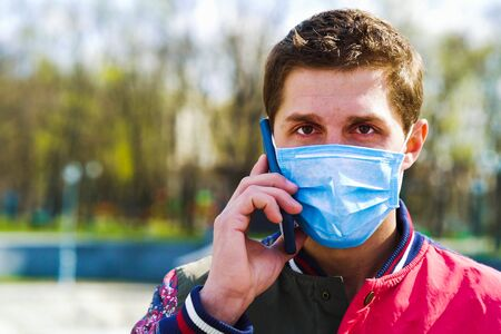 Young guy in medical mask talking on mobile phone in park 스톡 콘텐츠