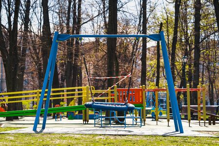 Swings with restriction tape on empty playground due to covid19 pandemic