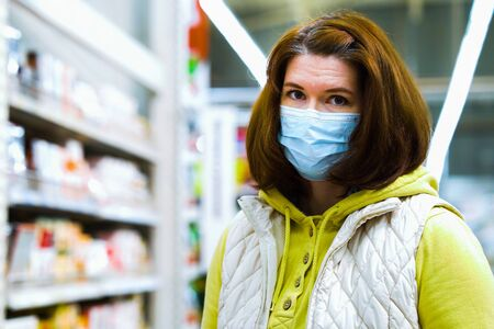 Portrait of young woman in medical mask in supermarket during COVID pandemic