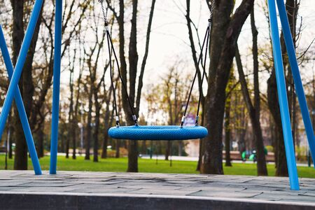 Swings swaying on empty playground during COVID pandemic