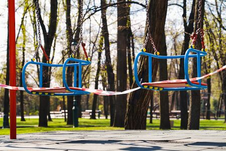Restriction tape on children swings during state of emergency due to COVID