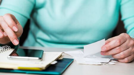 Female hands checking bills and writing down expenses