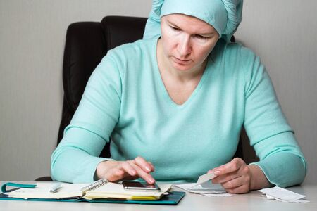Woman in headscarf checking bills and writing down expenses