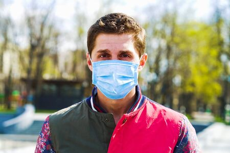 Young man wearing medical mask standing in park and looking at camera