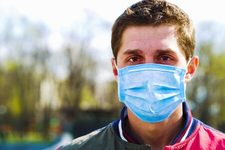 Portrait of young adult man wearing medical mask in park