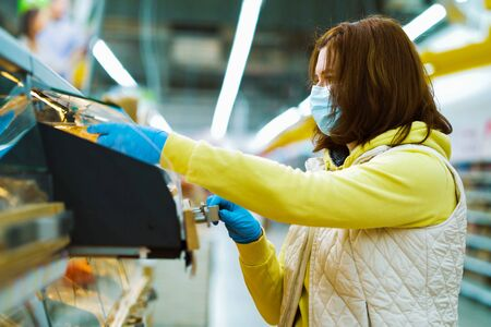 Girl in medical mask and gloves opening shelf with fresh bread in supermarket 스톡 콘텐츠