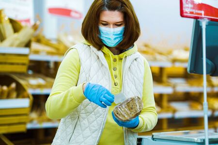 Girl in medical mask and gloves reading label of packed bread in supermarket