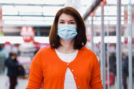 Attractive woman in medical mask posing at grocery store during COVID 스톡 콘텐츠