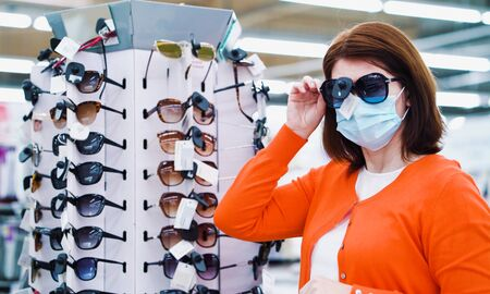 Yong woman in medical mask trying on sunglasses in shopping center