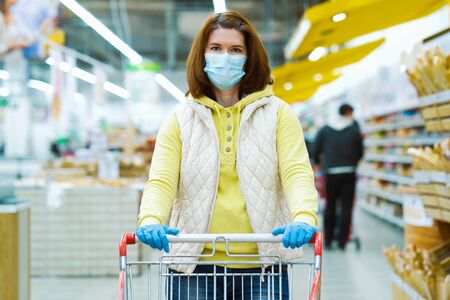 Young woman in mask and gloves with shopping cart in supermarket