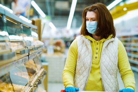 Young woman standing by fresh bread shelves at store during pandemic 스톡 콘텐츠