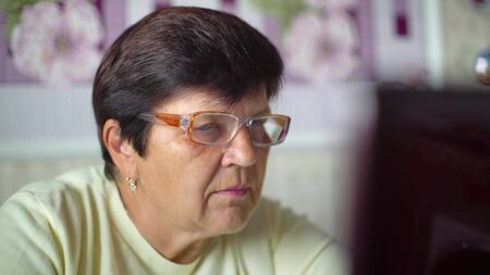 Senior old woman in eyeglasses surfing internet on laptop at home closeup
