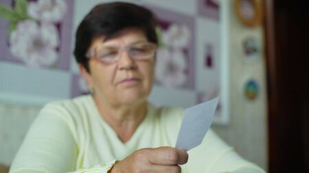 Defocused senior old woman in eyeglasses checking costs of daily expenses at home