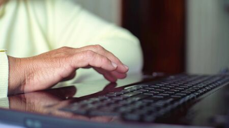 Closeup senior old woman hand on laptop keyboard surfing internet at home