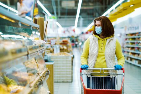 Girl walking with shopping cart along fresh bread shelves during pandemic