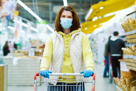 Young woman in medical mask with shopping cart at grocery store during pandemic