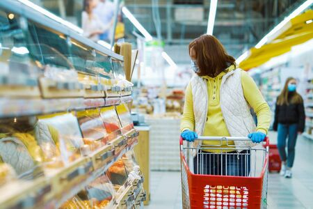 Woman with shopping cart by shelves with fresh bakery during pandemic