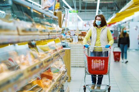 Young woman with shopping trolley at bakery during pandemic 스톡 콘텐츠