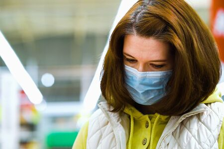 Customer in medical mask choosing products at grocery store during COVID-19