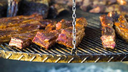 Crusty pork ribs roasting on grill outside