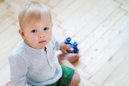 Baby boy sitting on floor and holding toy car