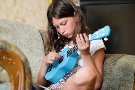 Lovely girl playing blue ukulele guitar at home