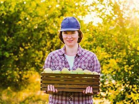 Female farmer carrying box of green apples in garden