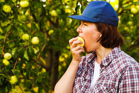 Young woman biting and chewing apple in orchard